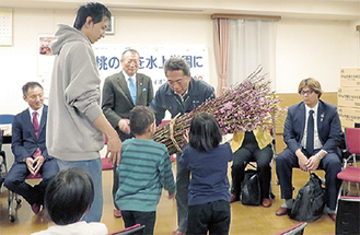 桃の花を渡す出川会長