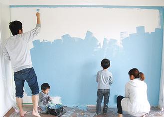 思い思いに壁を塗る親子