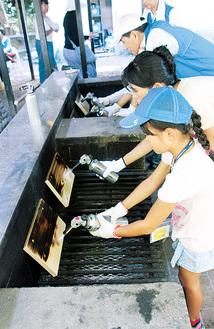 腐食を防ぐために板を焼く参加者