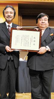 感謝状を手に取る伊坂理事長