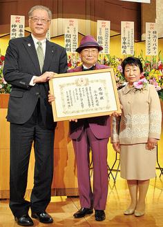 感謝状を持つ小山社長(中央)