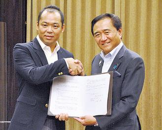 握手を交わす小泉社長(左)と黒岩知事