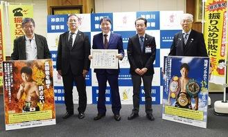 感謝状を手にする大橋会長(中央)らと、制作された井上選手のポスター