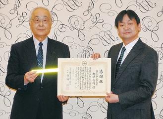 反射材を持つ板橋会長(左)と城所人事総務部長