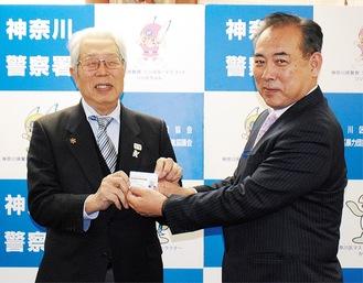 日下部署長(右)に免許証を渡す岡田さん
