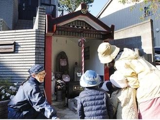 通りがかった園児と地蔵を眺める高野さん(左)