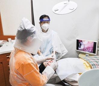 モニター越しに口腔内を確認する藤江院長(左)。患者とアシスタントの視線の先には鏡を設置し、映像を反射させて映し出している