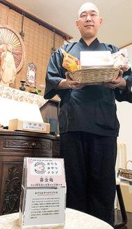 子どもたちへの「おすそわけ」の菓子を持つ浦上住職