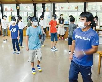 田中選手(右手前)の掛け声に応じて向きを変えるブラインドゲーム。アイマスクを着けた児童は徐々にばらばらの方向を向き出した
