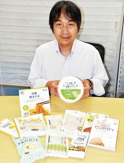新開発のカップ麺を持つ下坂さんと同社の商品