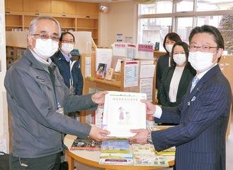 伊勢館長(左)に絵本を手渡す平本営業部長