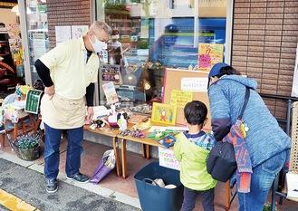 もってけマートの来場者と交流する佐藤さん(左)