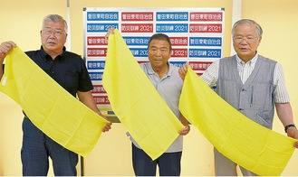 加入世帯に配布した黄色いタオルを持つ役員ら