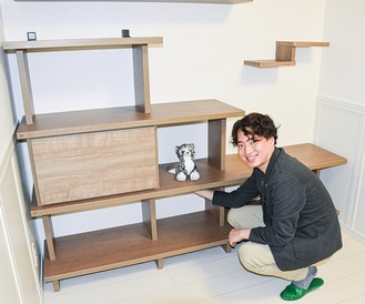 居室備え付けのシェルフを紹介する飯塚さん