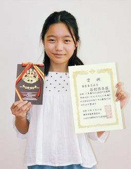 賞状と盾を持つ谷村さん