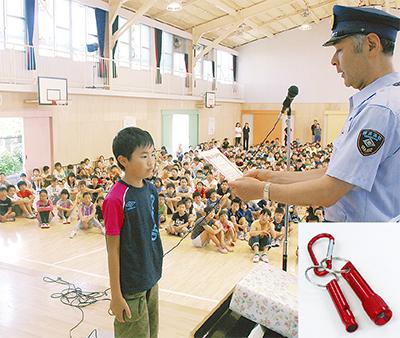 武笠署長から修了証を受け取る児童と記念品の防災グッズ