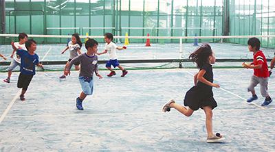 テニスコートで楽しく走る子どもたち