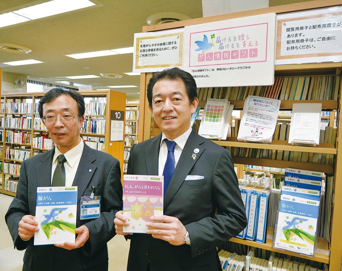冊子を手にする黒田会長と小室館長