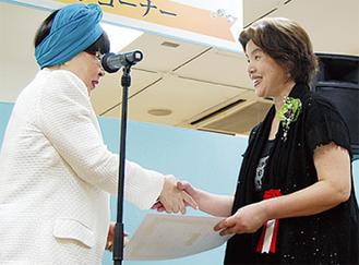 実行委員長の桂由美さんから表彰を受ける都倉さん(右)