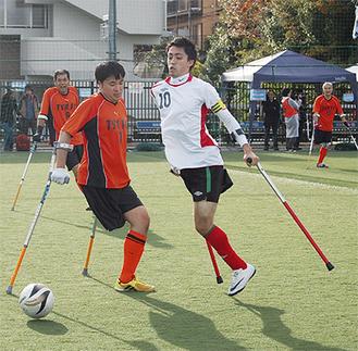 専用の松葉杖で体を支え、ボールを蹴る選手