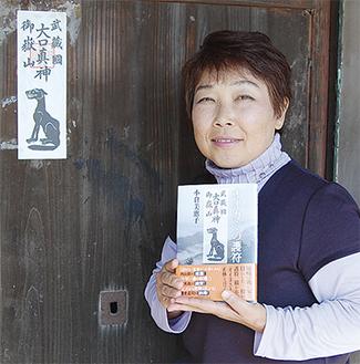 著書を持つ小倉美恵子さん。ドキュメント作品を作るきっかけとなった実家の「オイヌさま」の護符を前に