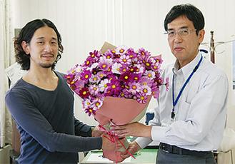 区長(左)に区の花を手渡す加藤さん(右)