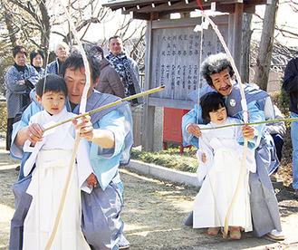 的に弓矢を放つ稚児の山田智大くん(左4才)と山田浩美さん(右3才)