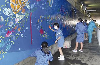 壁画清掃をする野川中生徒