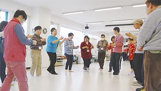 輪になって踊る西沢さんと利用者ら