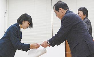 小嶋会長から表彰を受ける岩崎さん(左)