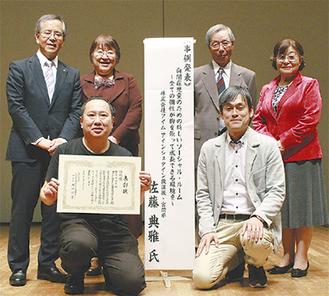 表彰状を手にほほ笑む佐藤代表(前列左)