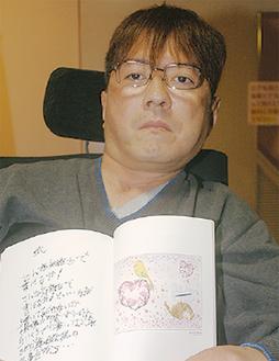 自作の詩の隣に絵が添えられている冊子をもつ松本さん