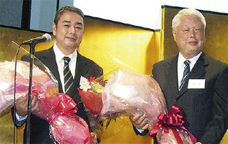 花束を持つ恵一郎氏(左)と昌一氏(右)