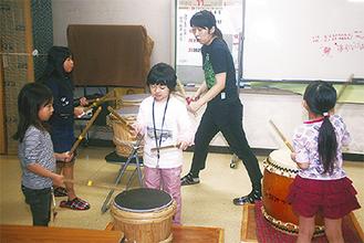 子どもたちに教えながら太鼓を叩く内田さん