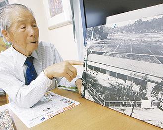 昭和38年の園舎の写真を見ながら当時を振り返る忠男さん