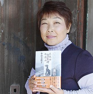 著書『オオカミの護符』を持つ小倉さん