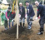 ソメイヨシノの苗木に土をかける市長ら