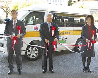 車両の前でテープカットをする持田副会長(中央)、平山施設長(右)、社協の奥山慶三事務局長