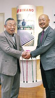 握手をかわす佐藤会長と柳澤社長(右)