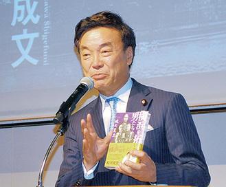 新著を手に講演する松沢氏
