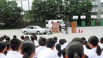 再現された事故現場に見入る生徒