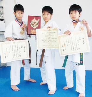 世界大会で優勝した松倉君(中央)とセミコンタクト大会優勝の新井君(左)、獅峯君(右)