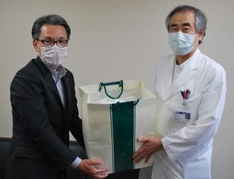 笹沼院長(右)にキャップを手渡す川田社長(左)