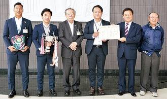 持田会長(右から2番目)から賞状を受け取る名池監督(同3番目)ら