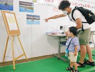 パラをテーマにした展示を見る親子