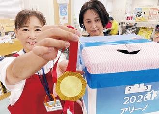 メダルと抽選箱を手にするスタッフ