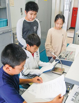 放送室で録音する児童ら