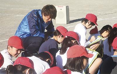 計算中の児童を覗き込む板倉選手