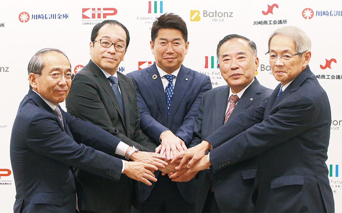 協定締結後、手を重ね合わせる出席者
