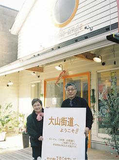 大山街道沿いのアンジェと鈴木克明さん(右)、寄里枝さん